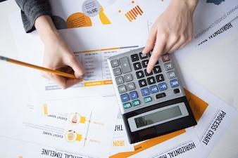 Mani femminili che lavorano con documenti e calcolatrice