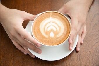 Mani femminili in possesso di tazza di caffè