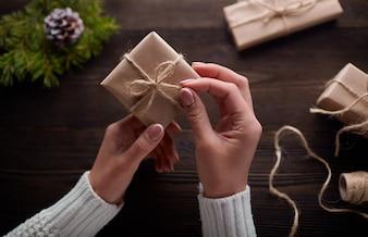 Mani in possesso di scatole di doni marrone con stringa