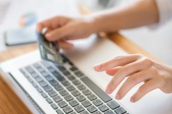 Mani in possesso di una carta di credito e utilizzo di computer portatile per lo shopping online
