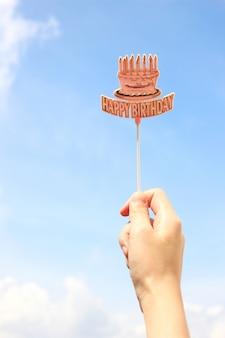 Mano che tiene felice compleanno con cielo azzurro