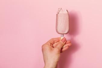 Mano di giovane donna in possesso di gelato su sfondo rosa. Sfondo di moda. Concetto estivo.