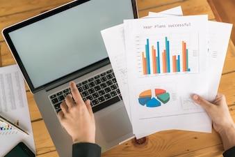 Mano donna di affari con grafici finanziari e computer portatile sul tavolo.