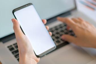 Mano donna di affari con grafici finanziari e telefono cellulare su laptop sul tavolo.