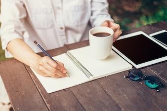 Mano giovane donna d'affari con la matita che scrive sul taccuino. Mano della donna con la matita che scrive sul taccuino e che lavora al caffè.