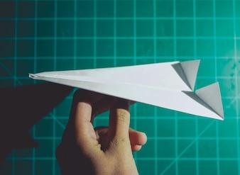 Mano in possesso di un aereo di carta sfondo di ingegneria
