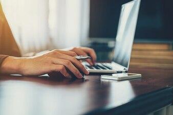 Mano uomo d'affari azienda mouse e l'utilizzo di laptop in ufficio. Effetto dell'annata.
