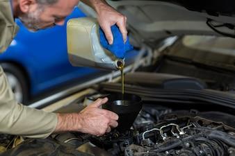 Meccanico di olio versando in motore di automobile