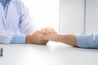 Medico che tiene la mano del paziente e rassicura il suo paziente maschio aiutando il concetto di mano.