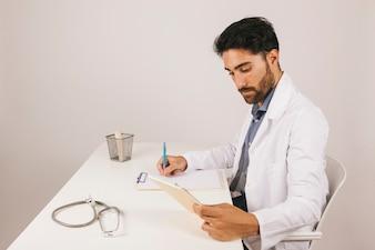 Medico concentrato che lavora alla sua scrivania