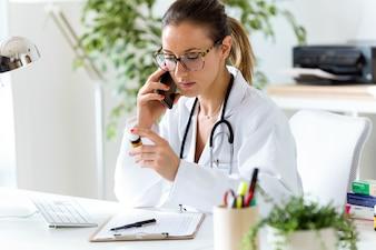 Medico di sesso femminile con il suo telefono cellulare in ufficio.