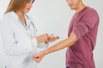 Medico femminile che prende sangue dal paziente