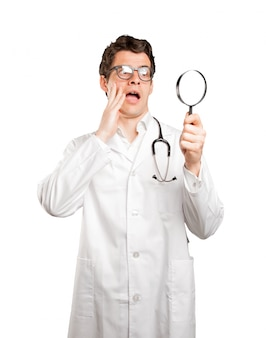 Medico sorpreso utilizzando una lente di ingrandimento su sfondo bianco