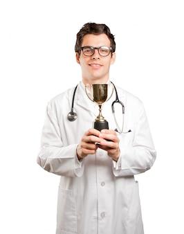 Medico vincitore con una tazza d'oro contro sfondo bianco