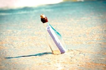 Messaggio in una bottiglia sulla spiaggia