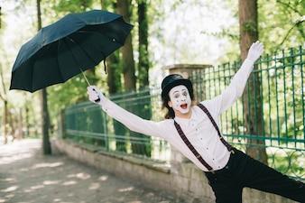 Mime cercando di volare con un ombrello