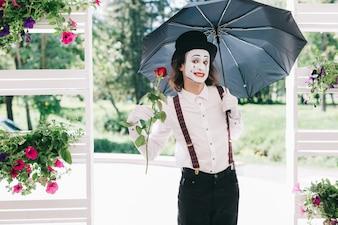 Mime che tiene un ombrello e una rosa