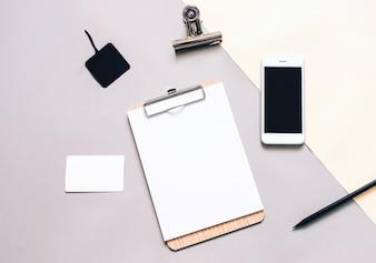 Mock up business di cancelleria, appunti in bianco e smartphone, stile minimo