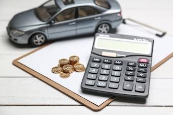 Modello di auto, calcolatrice e monete sul tavolo bianco