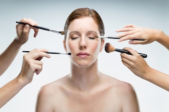 Molte mani applicare il make-up alla donna glamour su sfondo bianco.