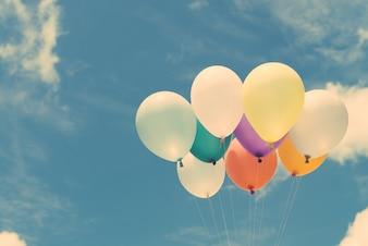 Molti palloncini colorati sul cielo blu, concetto di amore in estate e valentina, luna di miele di nozze. Immagini di stile d'effetto vintage.