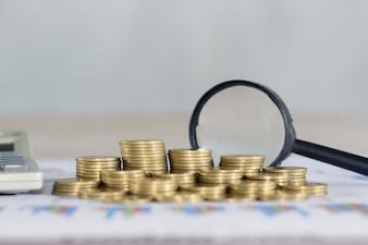 Monete stack, lente d'ingrandimento e calcolatrice sul grafico finanziario e grafico, background di contabilità. Concetto di denaro.