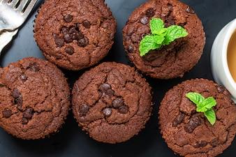 Muffin al cioccolato con menta su un tavolo di legno