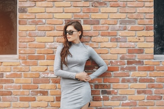 Muro di mattoni di modo della ragazza