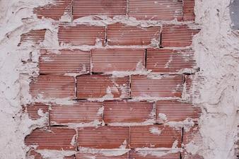 Muro di mattoni rossi con cemento bianco.