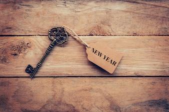 Nuovo anno sul tag con chiave sullo sfondo della tabella di legno.
