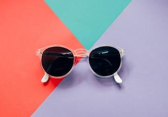 Occhiali da sole alla moda su sfondo minimalista colorato