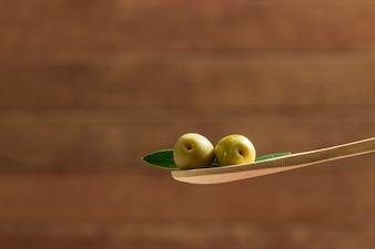 Olive su un cucchiaio di legno
