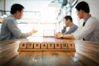 Parola di strategia sul tavolo di legno con team di lavoro team discussione insieme concetto in background.