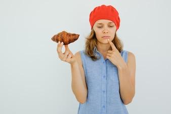 Pensierosa donna bella tenendo croissant delizioso