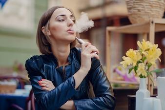 Pensieroso donna che gode della sua sigaretta elettronica