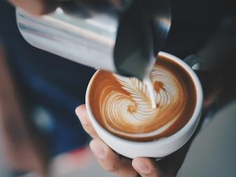 Persona che serve una tazza di caffè con una brocca di metallo
