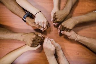 Persone che tengono le mani sul tavolo
