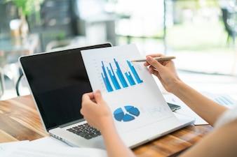 Persone d'affari che utilizzano computer portatile e grafici finanziari presso l'ufficio riunioni
