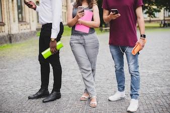 Persone in piedi tenendo notebook guardando smartphone