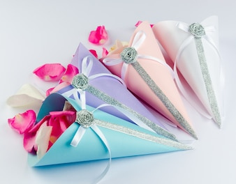 Petali di rosa in coni di confetti con archi in nastro di raso