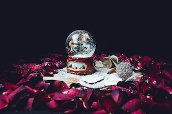Petali di rosa rossi circondano palla di vetro di Natale con neve