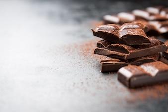 Pezzi di cioccolato su un tavolo in legno e cacao spruzzato