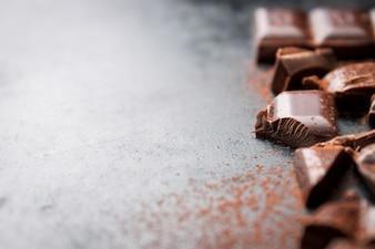 Pezzi di tavoletta di cioccolato su un tavolo di legno nero e cacao spruzzato sulla parte superiore