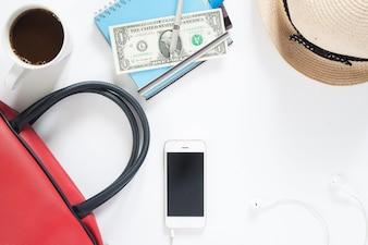 Pianale di dispositivo mobile, denaro, carta di credito, borsa a mano e caffè, concetto di viaggio e stile di vita, vista dall'alto