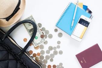 Pianta del concetto di viaggio con sacco a mano, soldi, carta di credito, telefono cellulare e passaporto su sfondo bianco