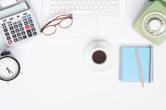 Piatto piano della scrivania di lavoro con il computer portatile bianco, la cancelleria e la tazza di caffè