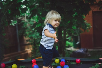 Piccolo neonato su un trampolino con palle colorate