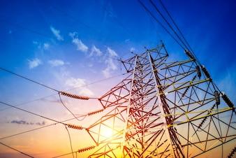 Piloni di elettricità al tramonto arancione
