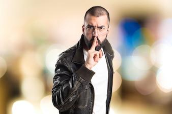 Pimp uomo facendo gesto di silenzio su sfondo unfocused