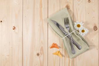 Posate e fiori sul tavolo in legno